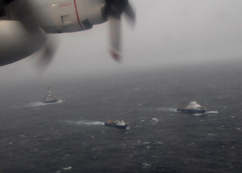 A Coast Guard HC-130 Hercules aircraft from Air Station Kodiak overflies the tugs Aiviq and Nanuq tandem towing the mobile drilling unit KullukSunday, Dec. 30, 2012. At the time of the photo, the tug Alert from Prince William Sound and the Coast Guard Cutter Alex Haley from Kodiak were en route to assist. U.S. Coast Guard photo by Petty Officer 3rd Class Chris Usher.