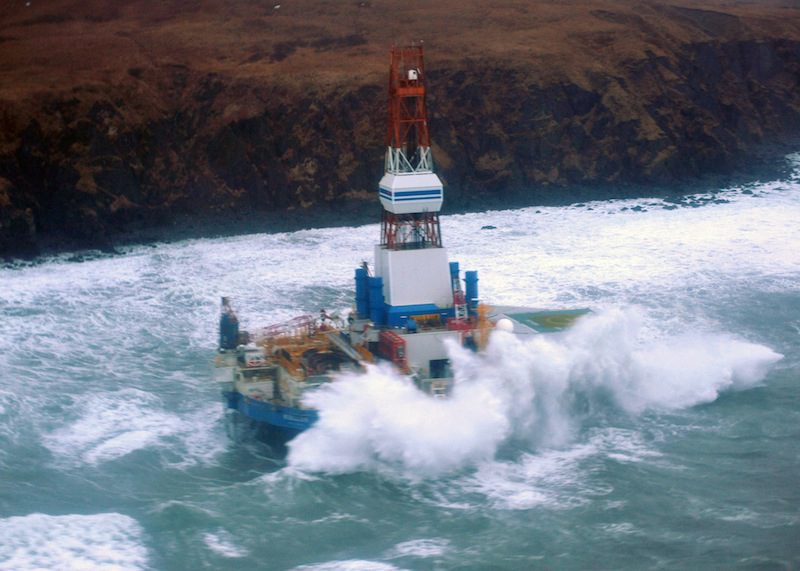 Waves crash over the conical drilling unit Kulluk where it sat aground on the southeast side of Sitkalidak Island, Alaska, Jan. 1, 2013. U.S. Coast Guard photo by Petty Officer 3rd Class Jonathan Klingenberg.