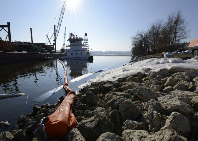 LECLAIRE, Iowa - The towboat Stephen L. Colby sits boomed off on the right descending bank of the Mississippi River near downtown LeClaire while response crews conduct cleanup and salvage operations, Dec. 1, 2013. U.S. Coast Guard Photo